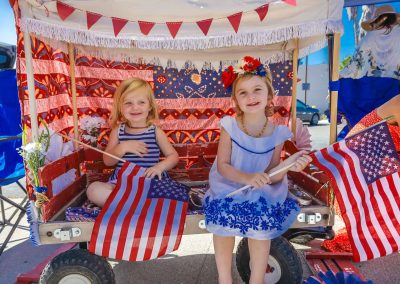 Ojai girls enjoying the 4th of July Parade from a festive bohemian inspired wagon